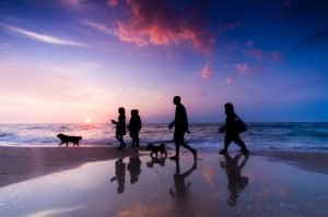 Family Walking Along Coast During Sunset