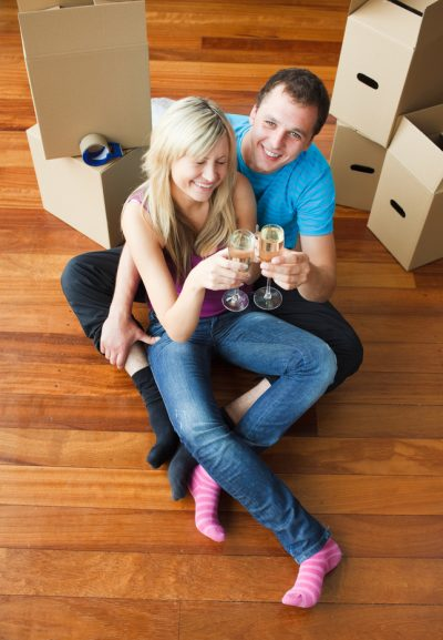 Happy Young Couple Celebrating Move with Champagne