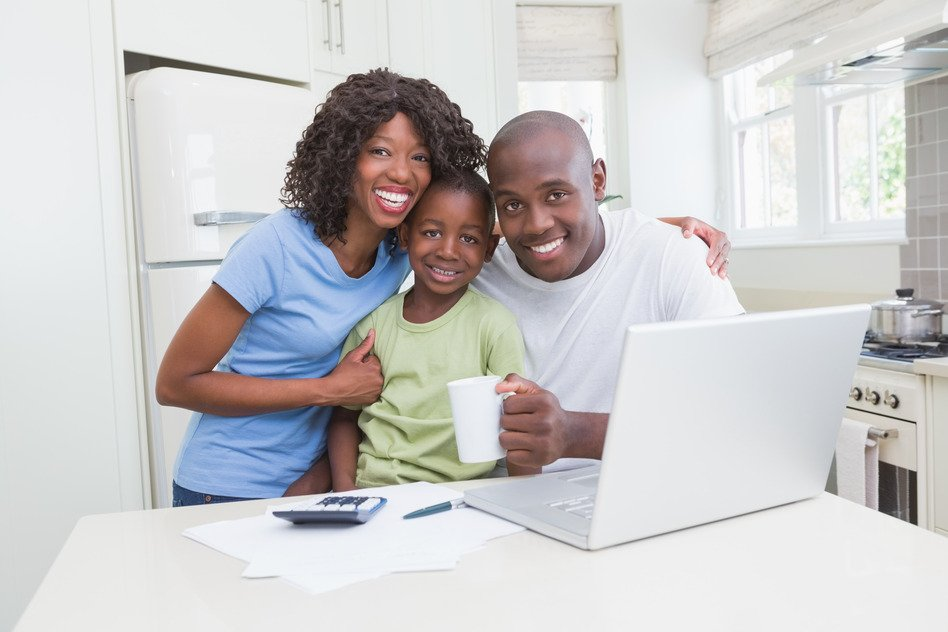 Family in Kitchen Smiling Next to Computer