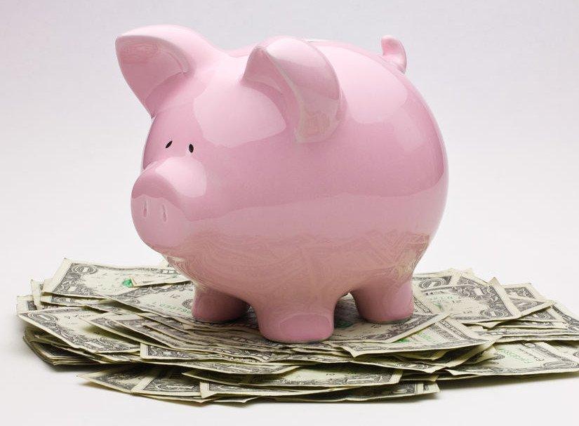 Pink Piggy Bank on Pile of Dollar Bills