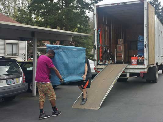 Two Movers Safely Hauling a Pad-Wrapped Furnishing