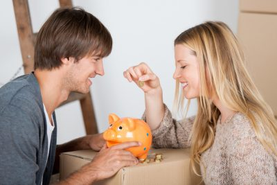A Couple Putting Coins into a Piggy Bank