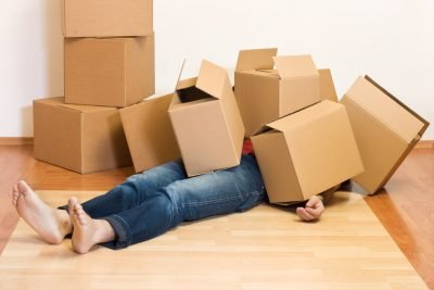 Person Laying Down Under Moving Boxes