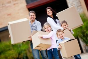 Parents and Kids Happily Carrying Boxes on Moving Day