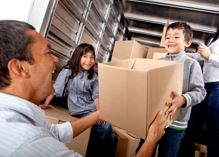 Happy Family Unloading Boxes from Moving Truck