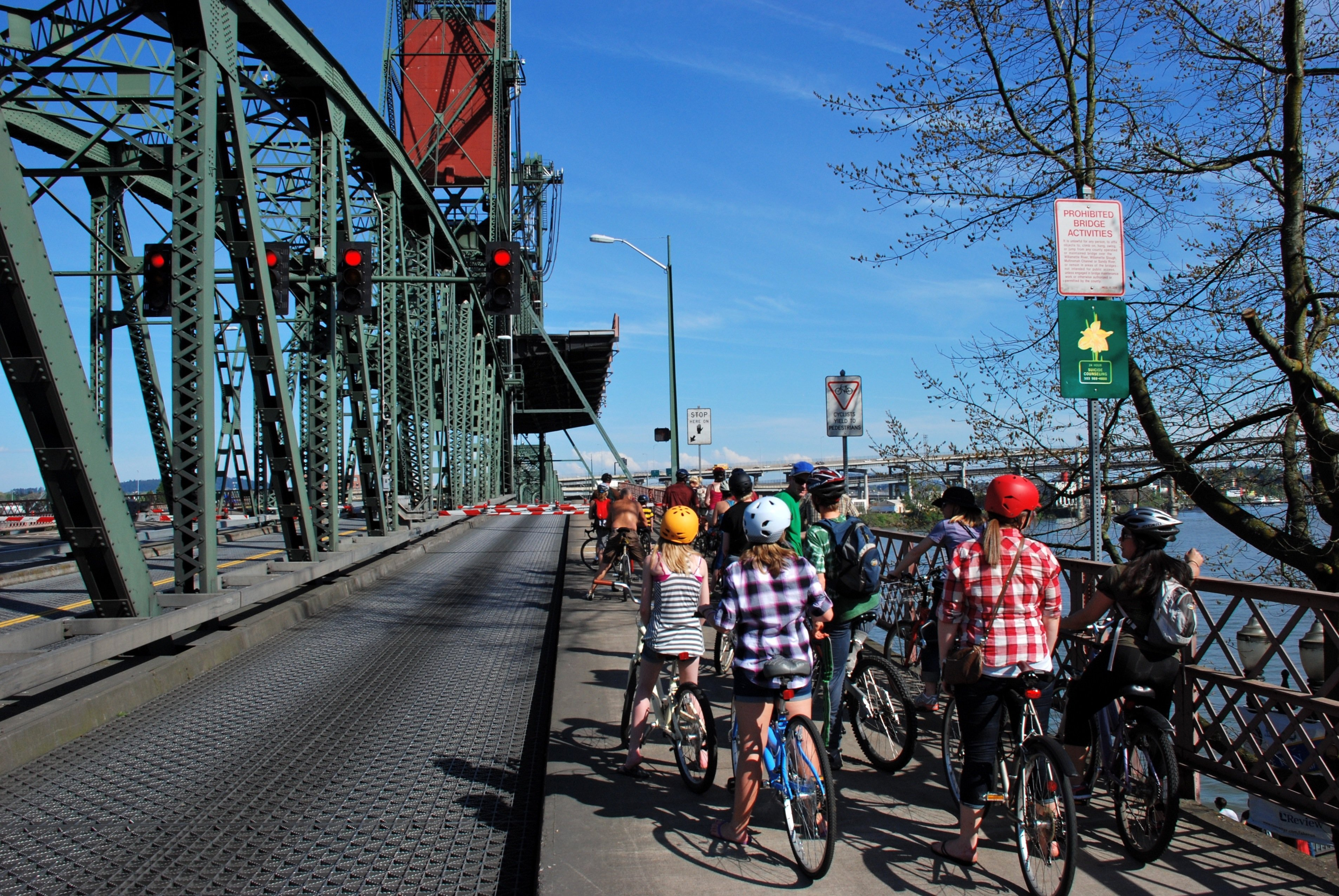 A group of cyclists waiting to cross the Hawthorne Bridge on a sunny day in Portland.