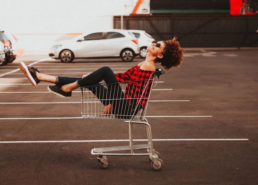 Woman in a shopping cart looking for the best place to buy moving boxes in Portland