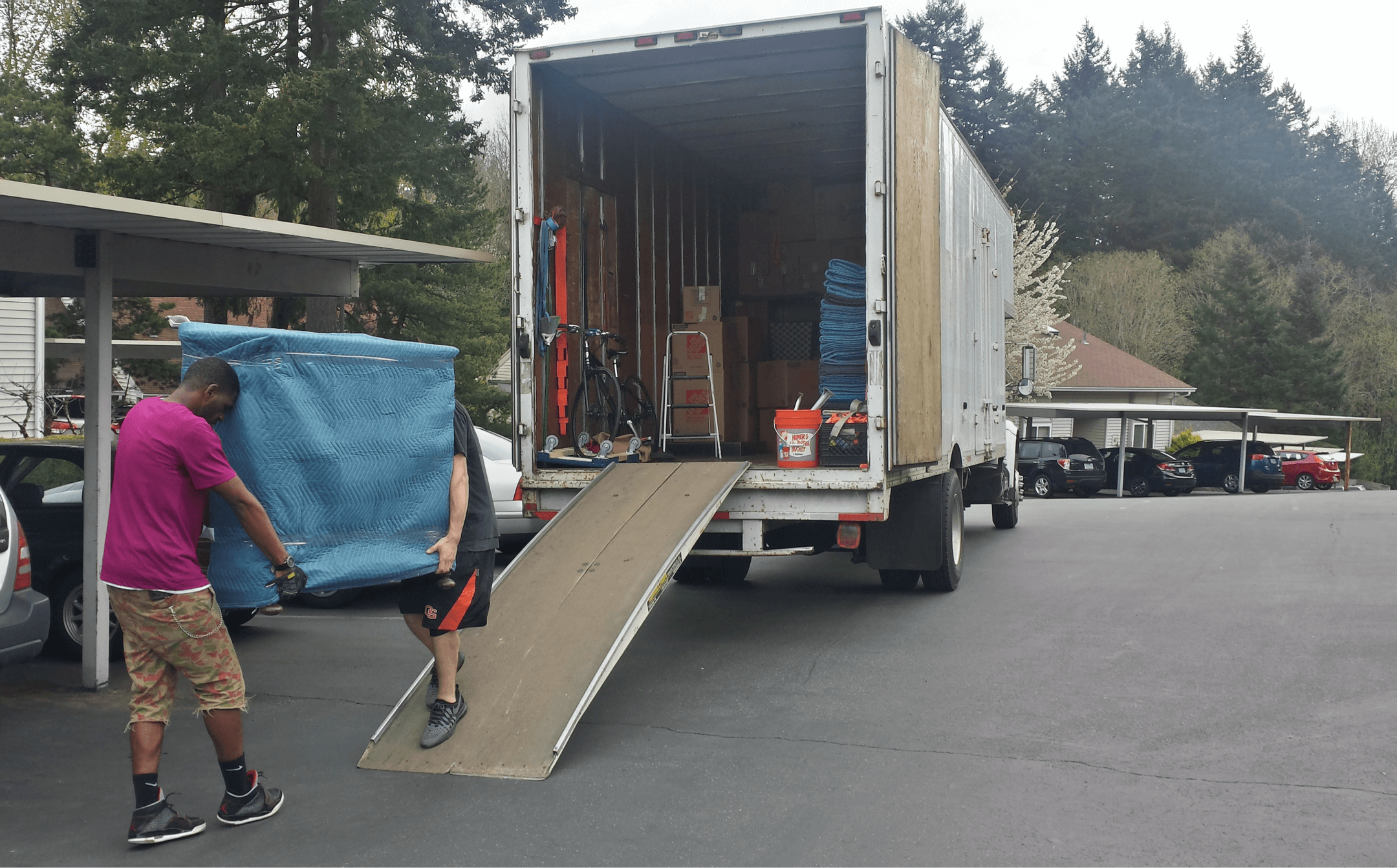 Priority movers lifting heavy furniture into moving truck