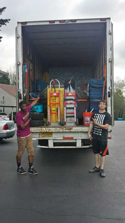 Priority movers standing next to packed moving truck