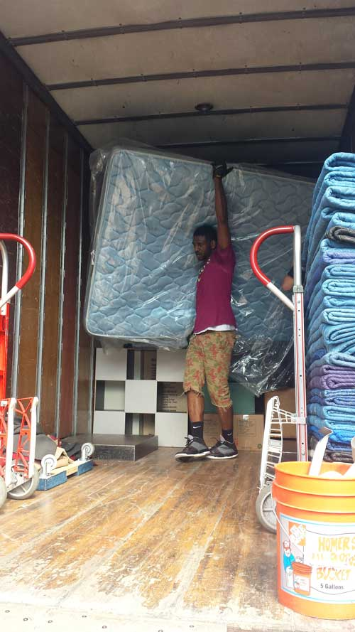 Priority mover lifting a mattress in the back of a moving truck