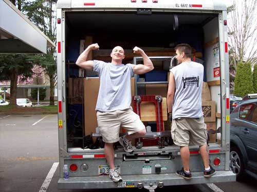 Priority mover showing his muscles while packing a moving truck
