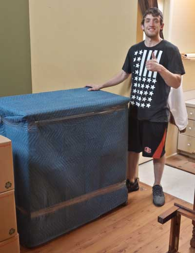 Priority mover giving thumbs up next to wrapped furniture
