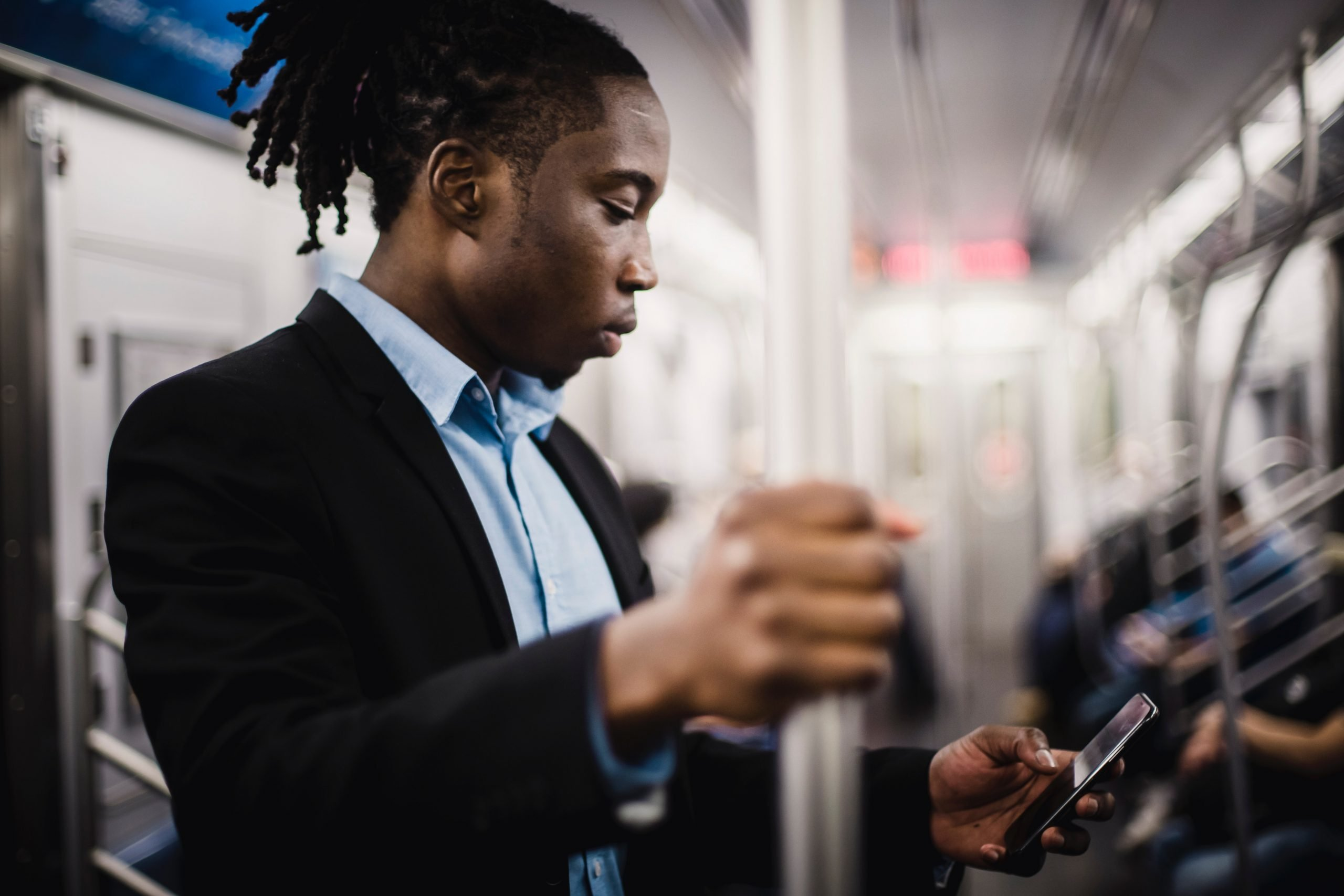Black man on bus, looking at phone and holding standing rail